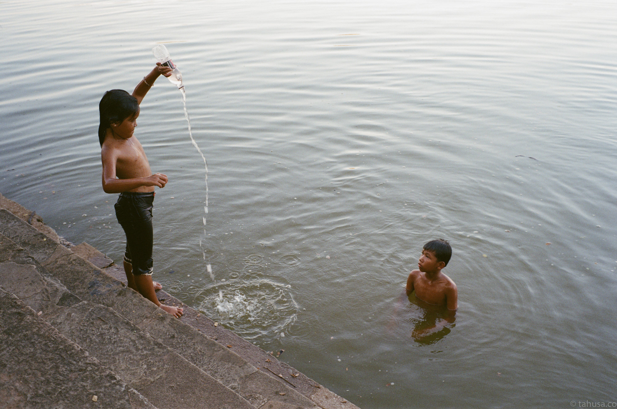 brother-and-sister-playing-around-outside-lake-dropping-water-cambodia-angkor-siem-reap-south-east-asia-travel-travelling-street-snap-using-leica-m2-summilux-35mm-f1.4-infinity-lock-pre-asph-analog-film-is-fuji-fujifilm-superia-premium-400-iso400