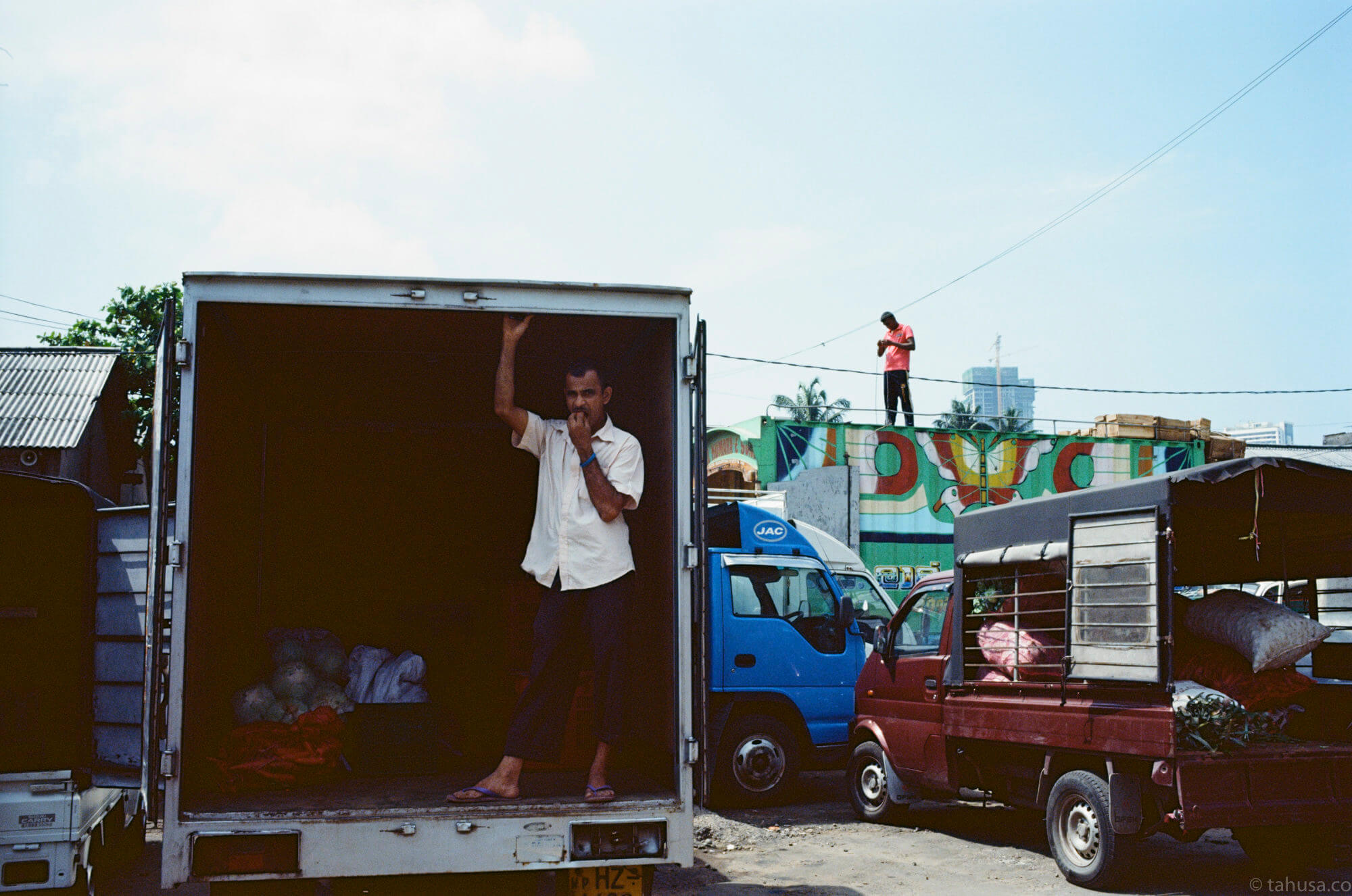 people-standing-inside-the-truck-and-the-other-men-standing-next-to-the-wire-in-colombo-sri-lanka-travel-photography-using-ektar-100-kodak-and-summilux-35mm-f1.4-asph-fle-leica-film