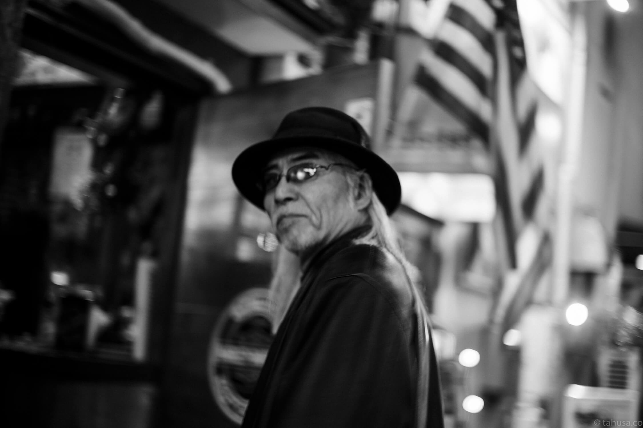 Cool-guy-with-sunglasses-at-night-time-inside-Goldengai-Golden-Gai-Famous-shinjuku-district-japan-street-tokyo-streetphotography-blackandwhite-BW-B&W-japanese-travel-with-Sony-A7-A7II-digital-camera-old-nokton-voigtlander-50mm-f1.5-1.5-prominent-mount-vintage