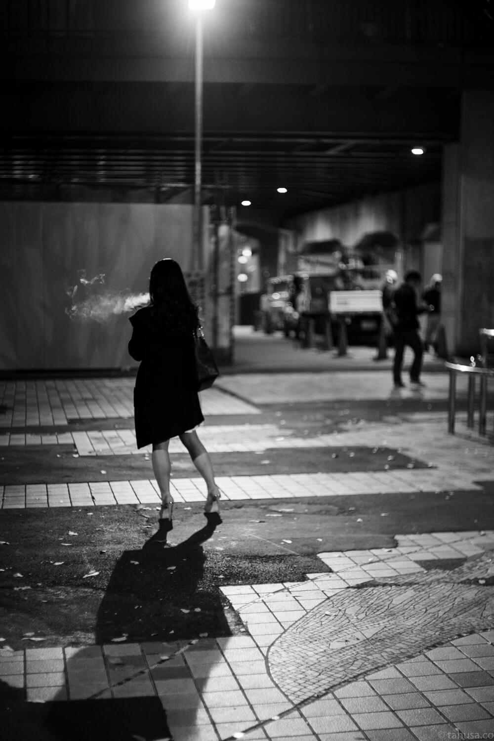 at-night-woman-was-having-a-cigarette-smoking-outside-shinjuku-district-japan-street-tokyo-streetphotography-blackandwhite-BW-B&W-japanese-travel-with-Sony-A7-A7II-digital-camera-old-nokton-voigtlander-50mm-f1.5-1.5-prominent-mount-vintage