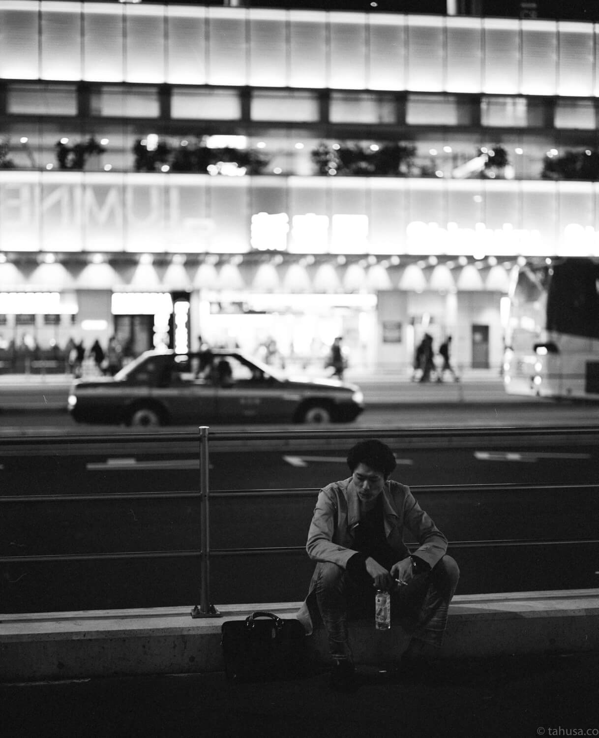 lonely-guy-sitting-on-bench-outside-JR-station-in-shinjuku-district-japan-street-tokyo-streetphotography-blackandwhite-BW-B&W-japanese-travel-with-pentax-67-6x7-mediumformat-medium-format-120-Delta-400-Ilford-Film-analog-105mm-f2.4-super-takumar