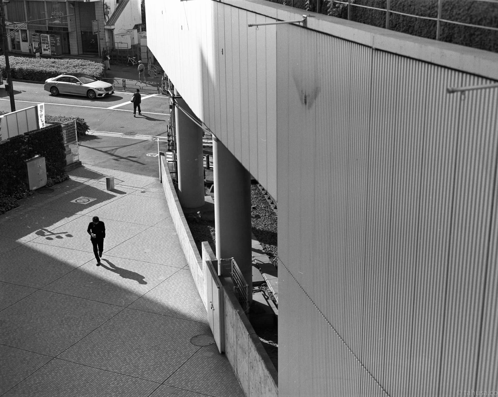 man-walking-under-sunlight-creating-shadow-in-shinjuku-district-japan-street-tokyo-streetphotography-blackandwhite-BW-B&W-japanese-travel-with-pentax-67-6x7-mediumformat-medium-format-120-Delta-400-Ilford-Film-analog-105mm-f2.4-super-takumar