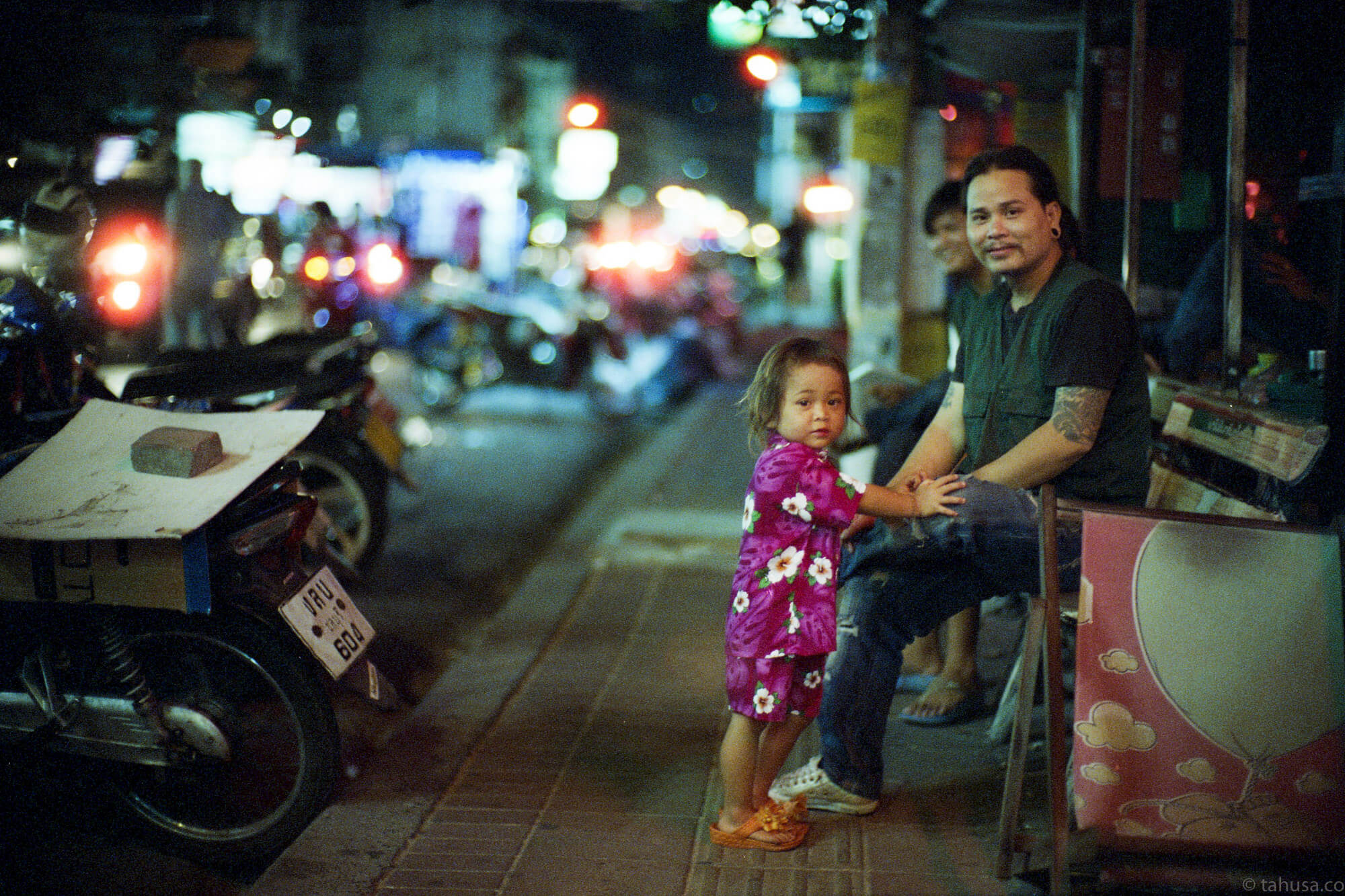 father-and-daughter-sitting-on-street-pattaya-thailand-HK-Cinestill-800T-800-iso800-Tungsten-film-movie-kodak-with-Noctilux-50mm-f1-f1.0-e58-v1-large-aperture-bokeh-grain-pushed-street-snap