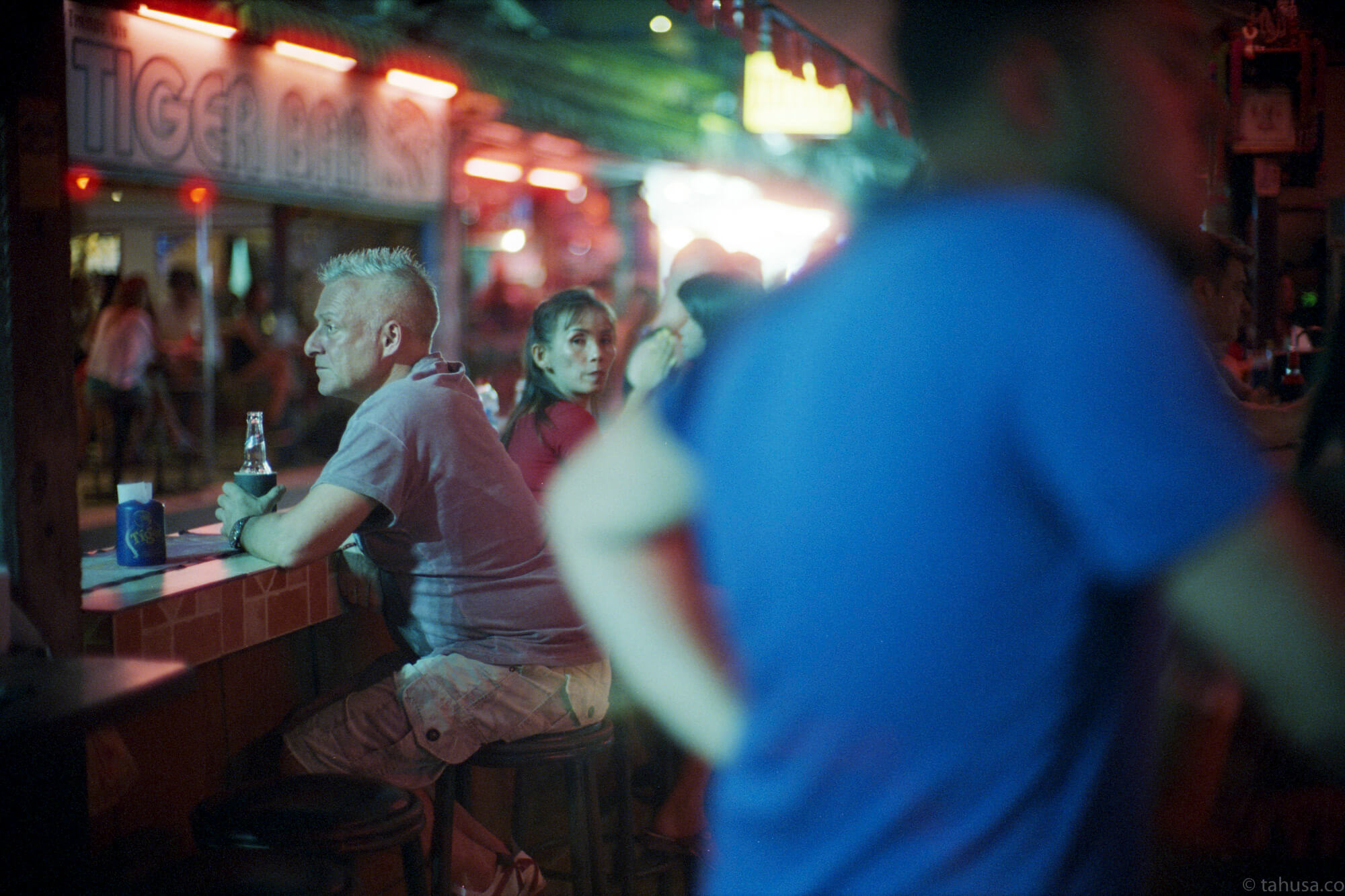 guy-enjoying-his-own-drink-alone-in-bar-pattaya-thailand-HK-Cinestill-800T-800-iso800-Tungsten-film-movie-kodak-with-Noctilux-50mm-f1-f1.0-e58-v1-large-aperture-bokeh-grain-pushed-street-snap