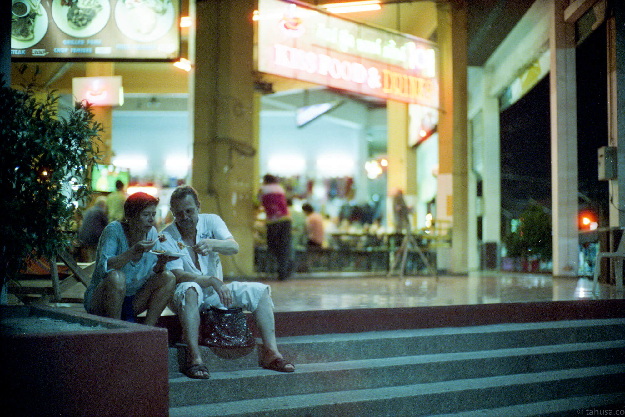 husband-and-wife-sharing-food-pattaya-thailand-HK-Cinestill-800T-800-iso800-Tungsten-film-movie-kodak-with-Noctilux-50mm-f1-f1.0-e58-v1-large-aperture-bokeh-grain-pushed-street-snap