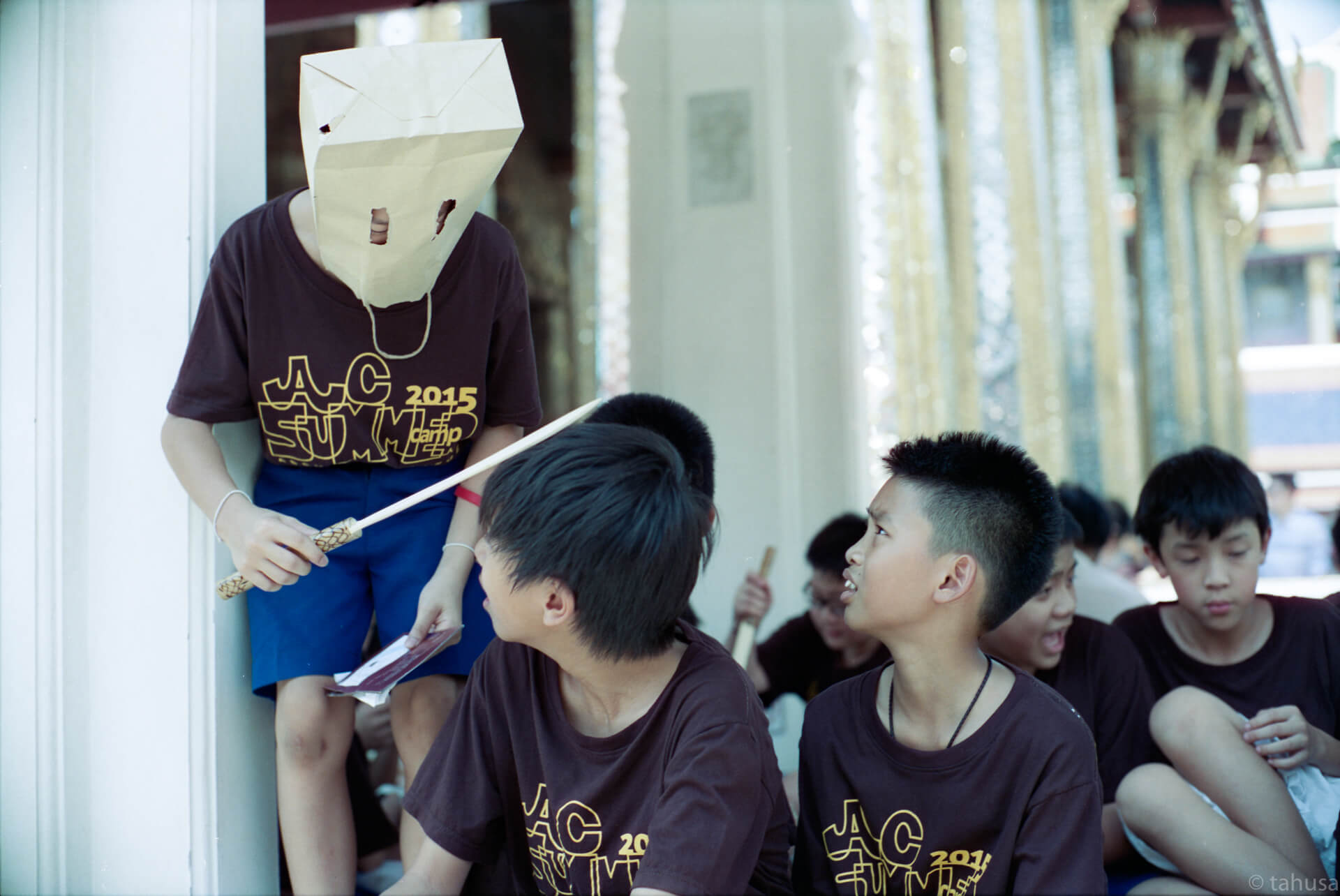 School-students-visiting-palace-in-bangkok-thailand-wearing-a-paper-bag-pretending-monster-with-shiny-gold-decoration-interior-street-snap-hk-cinestil-cine-cinestill50-50D-film-analog-leica-m2-Noctilux-50mm-f1-e58-v1