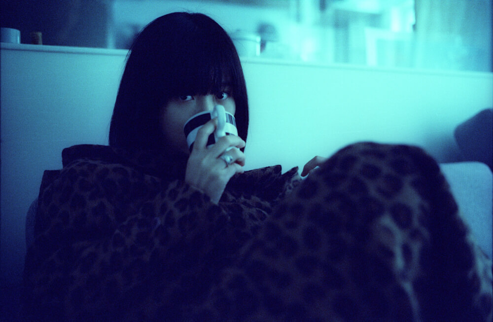 Ayu-home studio-holding cup-portrait-shy-Noctilux 50mm-CineStill 800T-Tungsten-film-snap