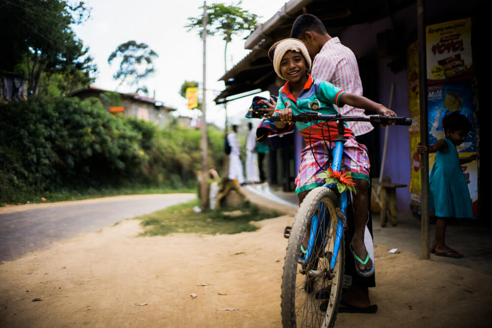 children-playing-with-bike-not-fit-happily-walk-pass-local-stores-in-ella-sri-lanka