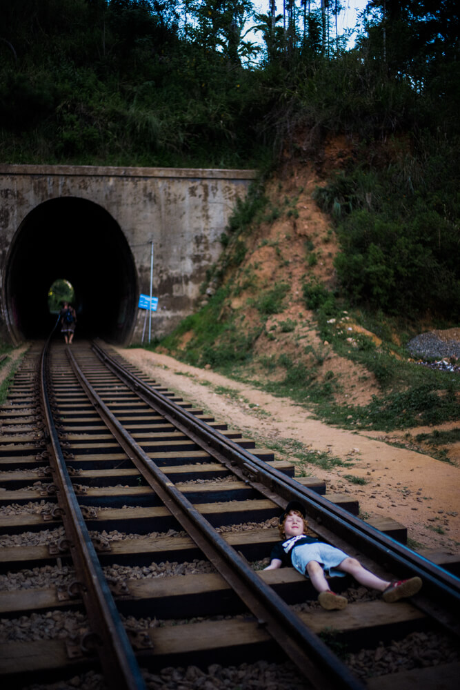people-waiting-for-train-to-arrive-lying-on-train-track-rail-tunnel-nine-arch-bridge-sri-lanka