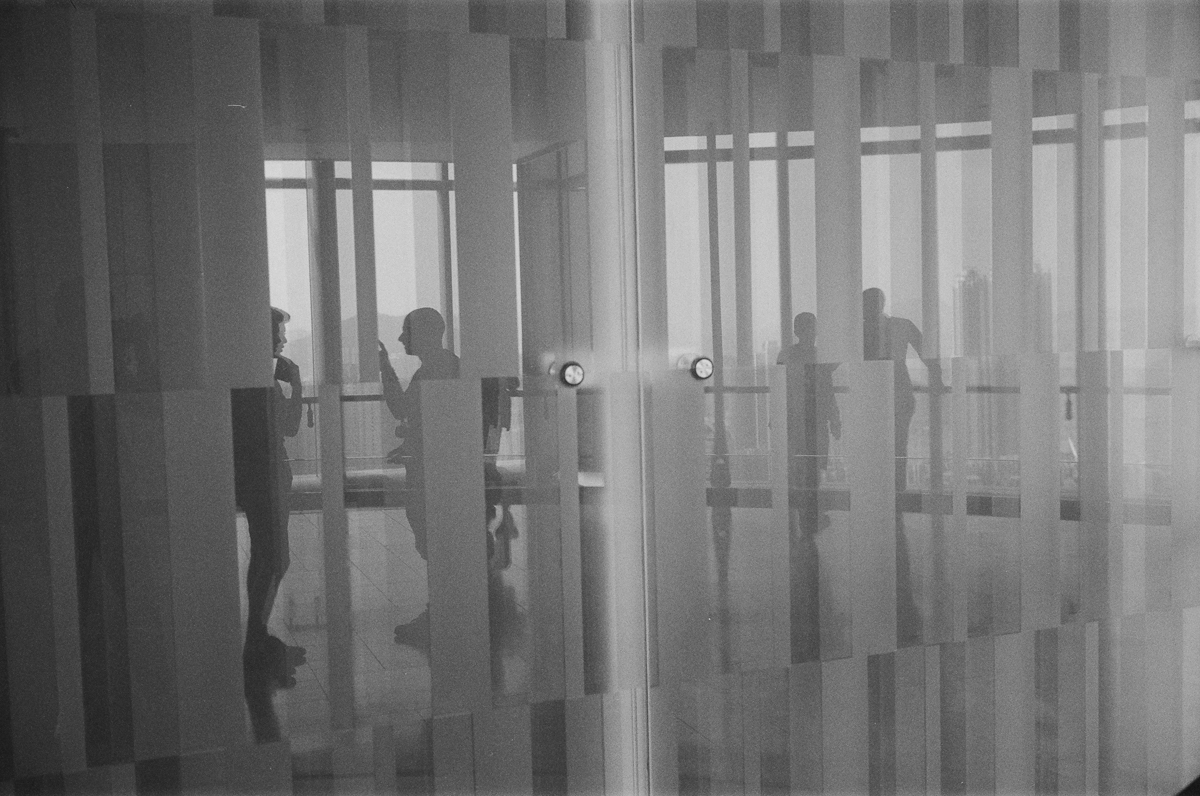 Everyone-is-chatting-in-Quarry-Bay-Reflection-of-the-wall-hong-kong-shutter-alliance-photowalk-Leica-Summicron-35mm-f2-IV-Ilford-Delta-400-black-and-white-bw-monotone