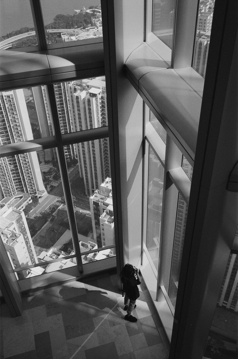 Quarry-bay-carmen-shooting-through-the-glass-window-hong-kong-shutter-alliance-photowalk-Leica-Summicron-35mm-f2-IV-Ilford-Delta-400-black-and-white-bw-monotone-monochrome-one-island-east