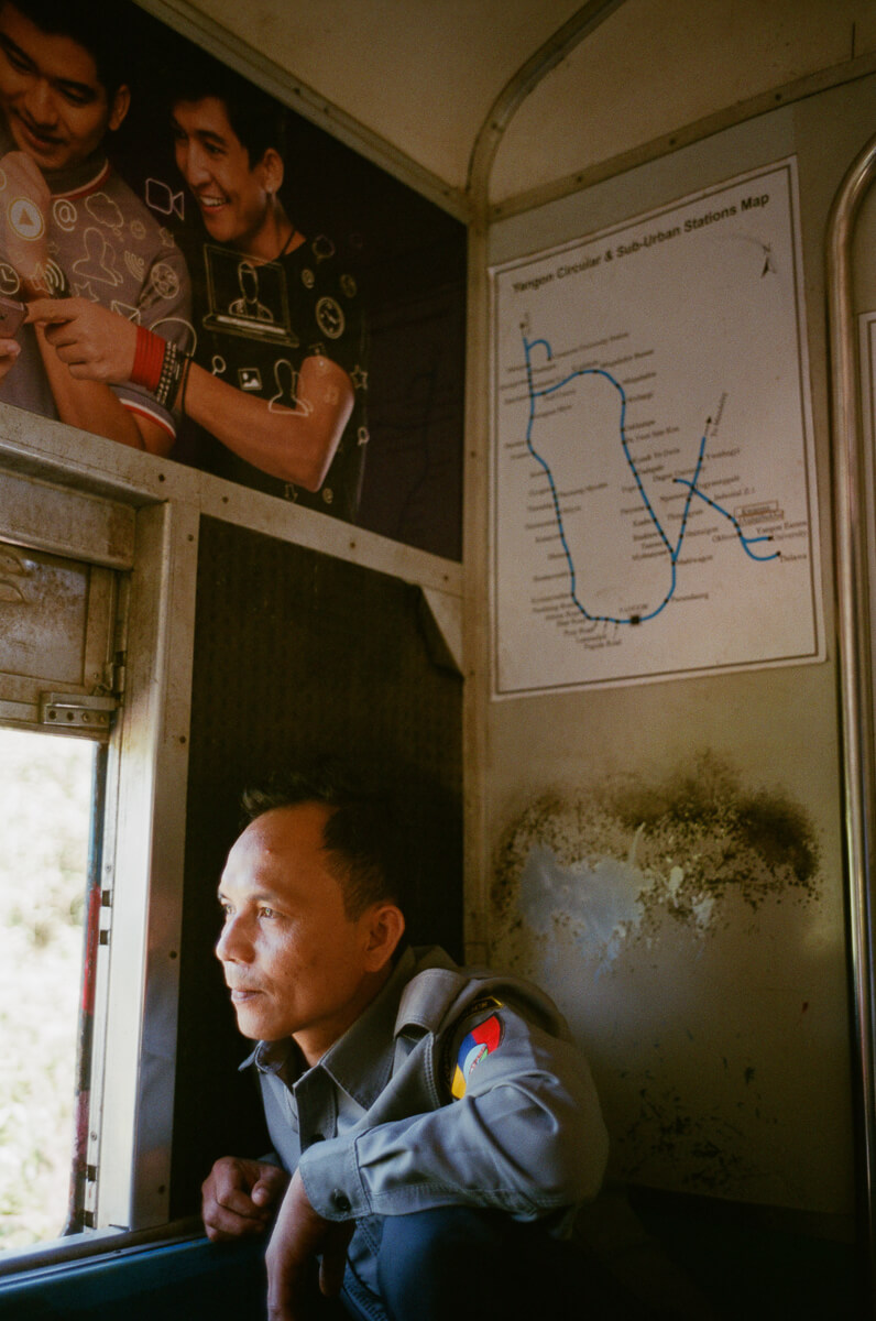 circular-train-guide-security-signal-sitting-there-looking-out-of-the-window-portrait-documentary-life-myanmar-yangon-35mm-f2-summicron-8elements-v1-leica-m2-Fuji-fujifilm-Superia-Premium-400-travel