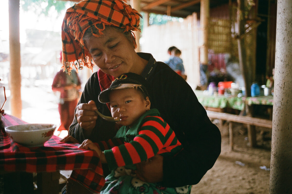grandma-feeding-baby-with-food-portrait-inle-lake-mynamar-travelling-city-cities-snap-burma-fuji-fujifilm-superia-premium-400-leica-camera-summicron-35mm-f2-v1-8elements