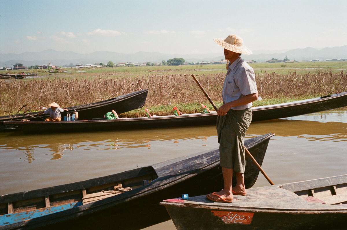 man-canoeing-sunny-weather-sunday-market-entrance-inle-lake-burma-myanmar-boat-trip-travel-analog-film-images-Fuji-fujifilm-Superia-Premium-400-8elements-v1-1