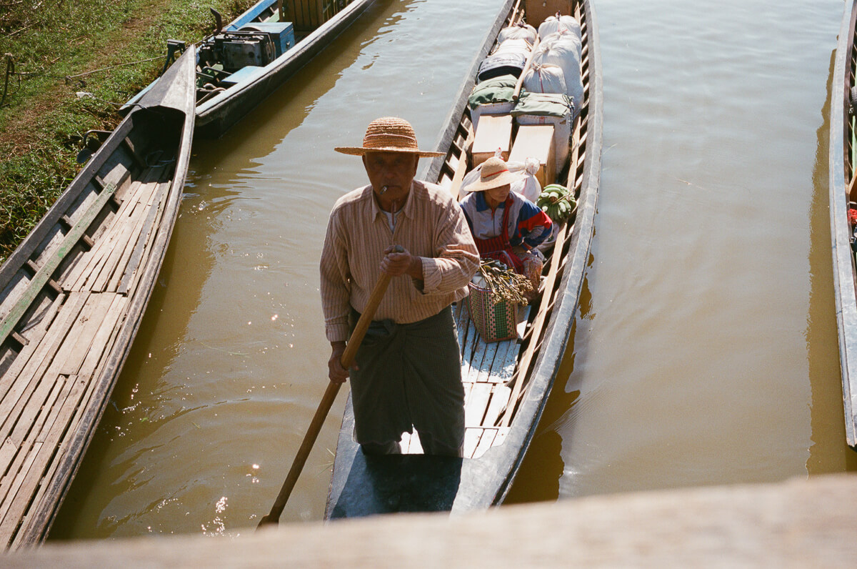 man-canoeing-towards-me-sunny-weather-sunday-market-entrance--waiting-for-people-transport-inle-lake-burma-myanmar-boat-trip-travel-analog-film-images-Fuji-fujifilm-Superia-Premium-400-8elements-v1-2