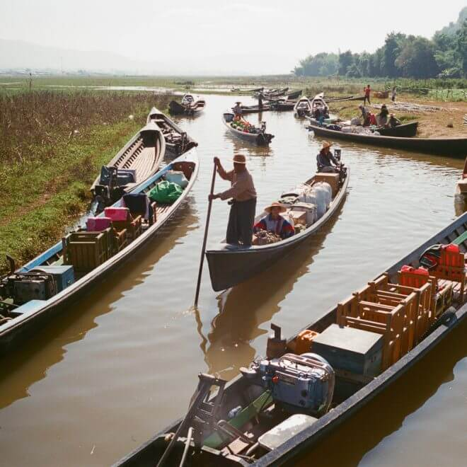 man-canoeing-towards-me-sunny-weather-sunday-market-entrance--waiting-for-people-transport-inle-lake-burma-myanmar-boat-trip-travel-analog-film-images-Fuji-fujifilm-Superia-Premium-400-8elements-v1