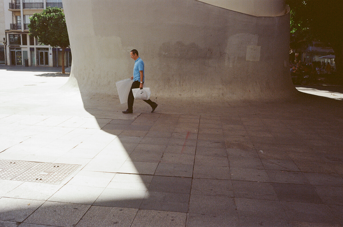 man-carrying-his-stuffs-travel-blog-visit-Sevilla-spain-Kodak-Ektar-100-film-analog-Summicron-35mm-f2-35-v1-8elements-seville
