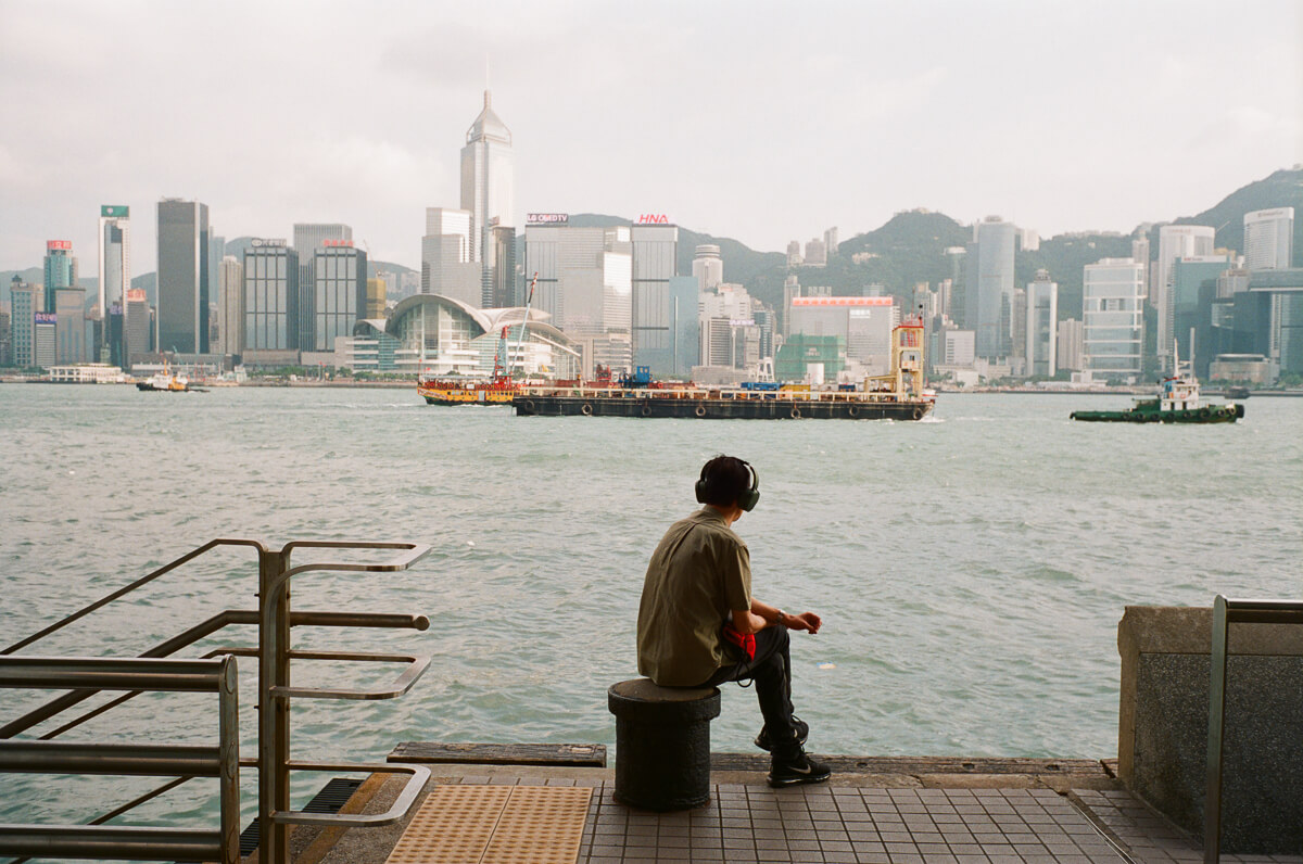 man-sitting-by-the-sea-listening-to-music-HK-Cultral-Centre-Hong-Kong-Tsim-sha-tsui-Superia-premium-400-fuji-fujifilm-film-analog-Leica-Summicron-35mm-f2-IV-7elements