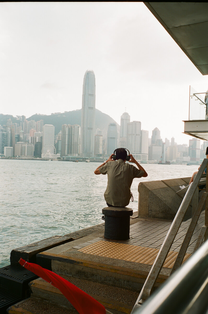 man-sitting-by-the-sea-listening-to-music-with-HK-Cultral-Centre-Hong-Kong-Tsim-sha-tsui-Superia-premium-400-fuji-fujifilm-film-analog-Leica-Summicron-35mm-f2-IV-7elements-2