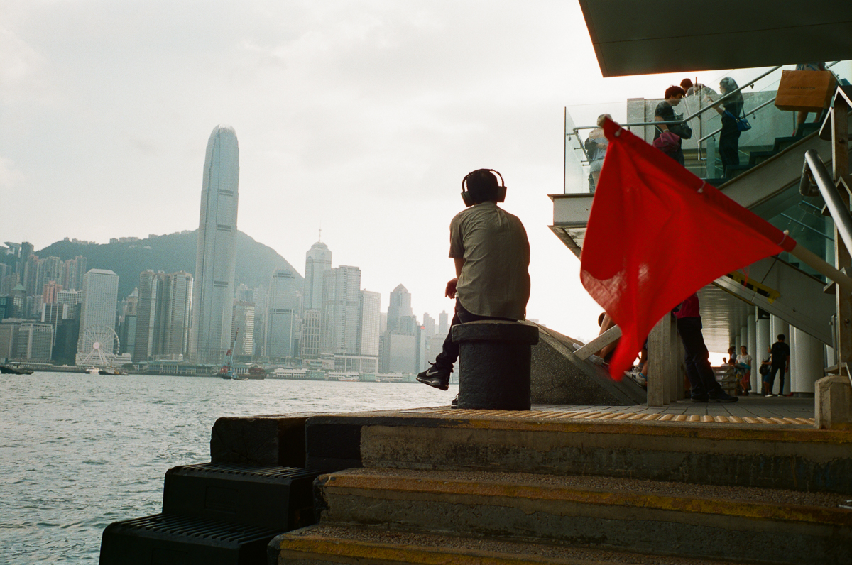 man-sitting-by-the-sea-listening-to-music-with-red-flag-HK-Cultral-Centre-Hong-Kong-Tsim-sha-tsui-Superia-premium-400-fuji-fujifilm-film-analog-Leica-Summicron-35mm-f2-IV-7elements-2