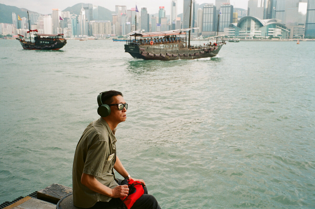 man-sitting-by-the-sea-listening-to-music-with-red-flag-HK-Cultral-Centre-Hong-Kong-Tsim-sha-tsui-Superia-premium-400-fuji-fujifilm-film-analog-Leica-Summicron-35mm-f2-IV-7elements-3