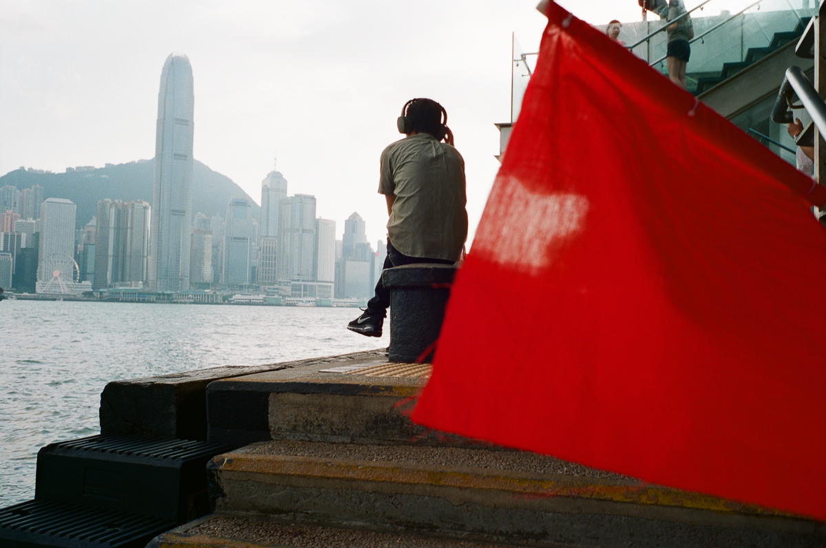 man-sitting-by-the-sea-listening-to-music-with-red-flag-HK-Cultral-Centre-Hong-Kong-Tsim-sha-tsui-Superia-premium-400-fuji-fujifilm-film-analog-Leica-Summicron-35mm-f2-IV-7elements
