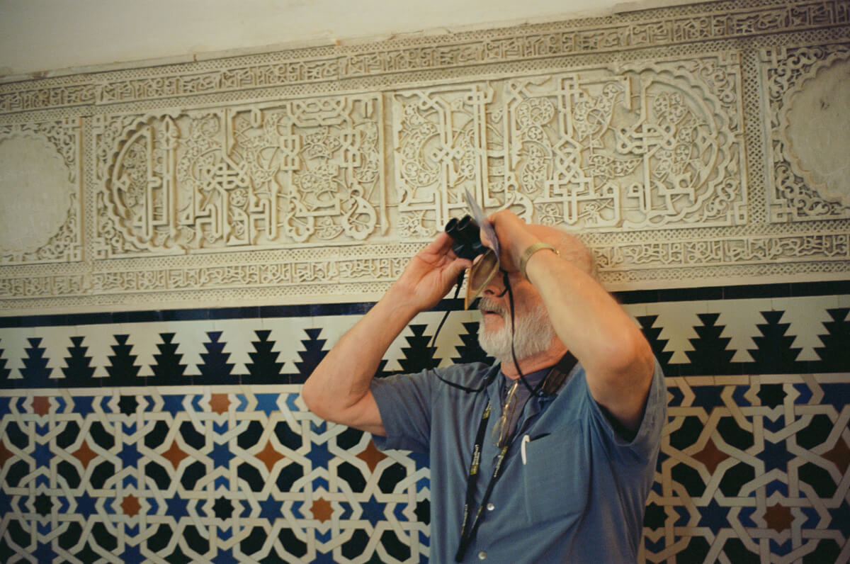man-using-binocular-inside-museum-architecture-archit-travel-blog-visit-Sevilla-spain-Kodak-Ektar-100-film-analog-Summicron-35mm-f2-35-v1-8elements-seville