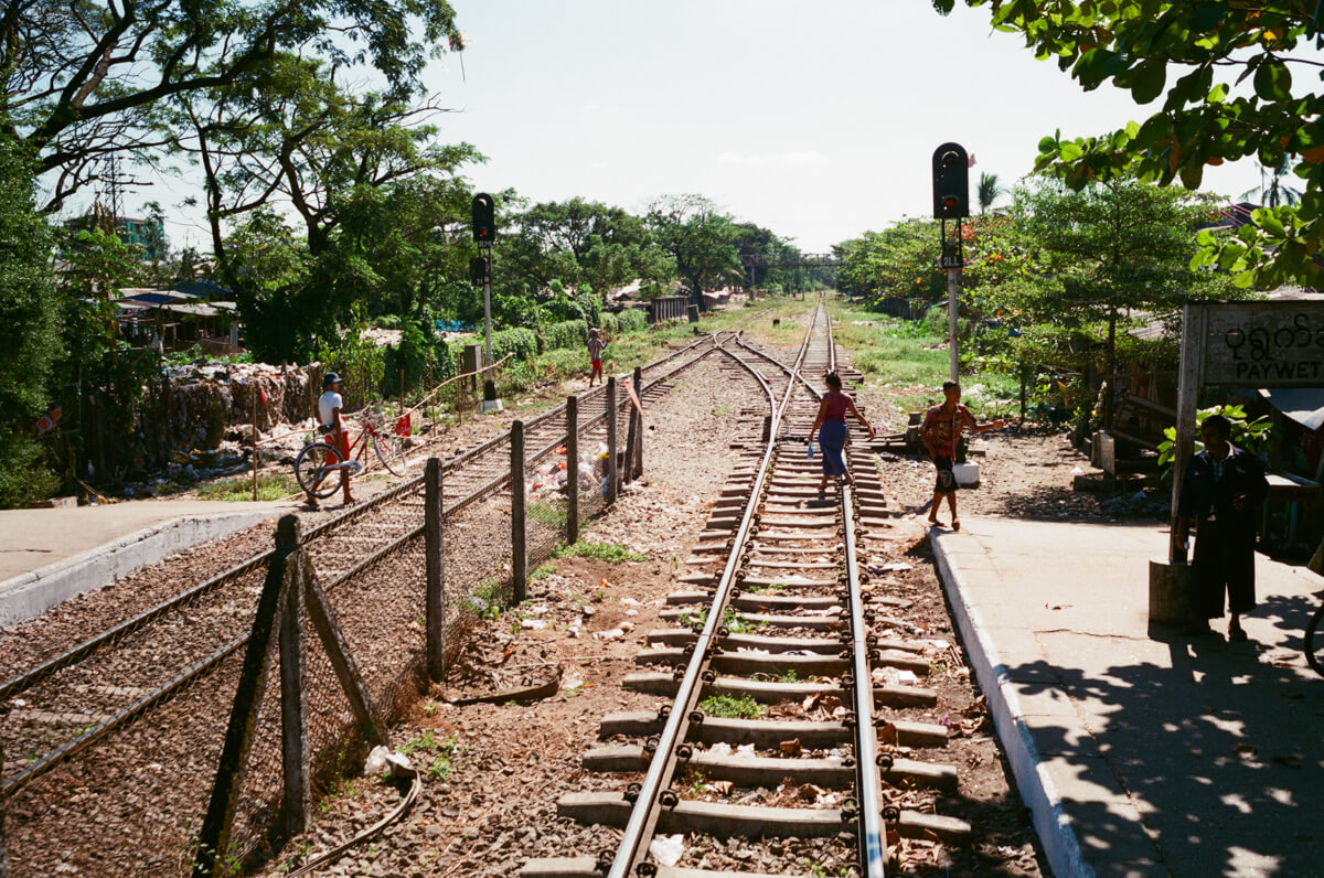 Burmese-crossing-railway-tracks-sunny-afternoon-superia-premium-yangon-myanmar