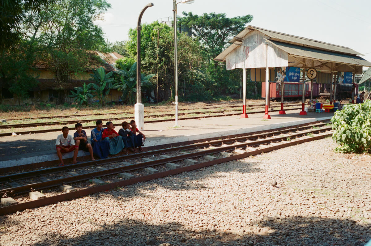 Burmese-people-sitting-outside-train-station-yangon-circular-train-myanmar-sunny-weather-superia-premium-400