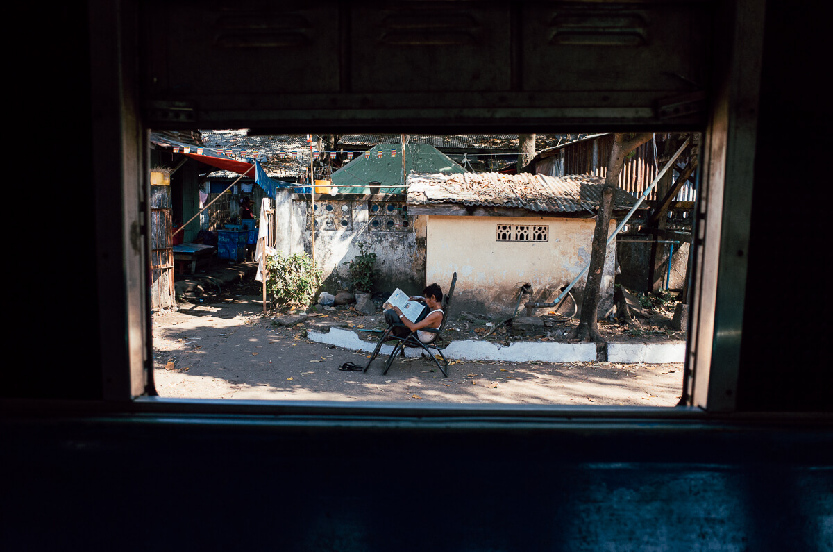 Man-reading-newspaper-outiside-window-of-circular-train-yangon-myanmar-what-you-can-take-from-train
