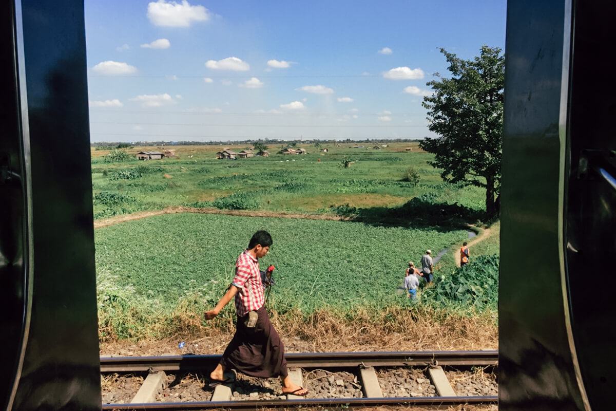 People-walking-along-train-tracks-in-circular-train-yangon-myanmar-scenery-view-from-train-window