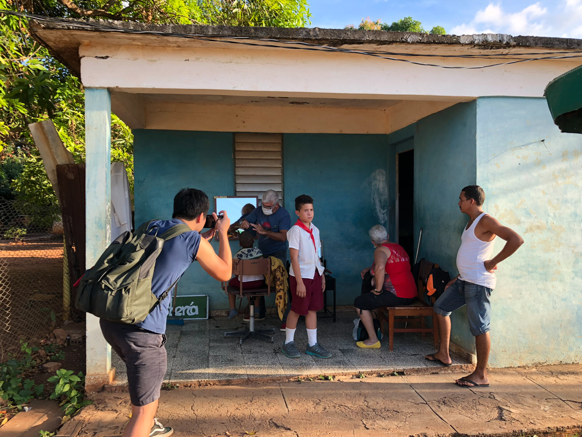 Behind-the-scene-i-was-capturing-pictures-of-local-in-Trinidad-barber-shop-travelling-in-central-america-filson-backpack-magnum
