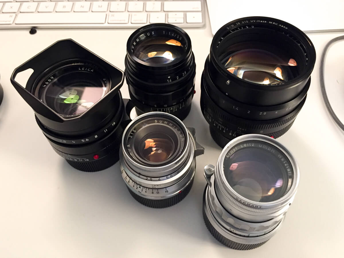 vintage-leica-lenses-on-table-with-summilux-11663-FLE-Steel-rim-35mm-1.4-noctilux-50mm-f1-e58-v1-goggle-MS-optica-35mm-f3.5-50mm-1.4-v2-kanto-repainted-summicron-35mm-f2-v1
