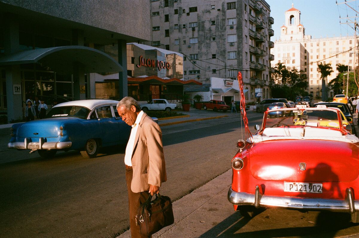 black-man-under-sunshine-next-to-colorful-vintage-car-centro-havana-cuba-agfa-vista-400-leica-film-analog-35mm-summilux-1.4-asph-fle-street-guide