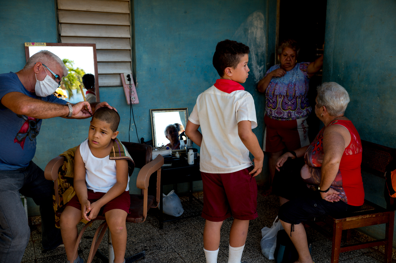 shot-with-kids-children-adults-sitting-together-in-barber-shop-salon-cuba-cienfuegos-travel-leica-m10-summicron-35mm-iv-v4-f2
