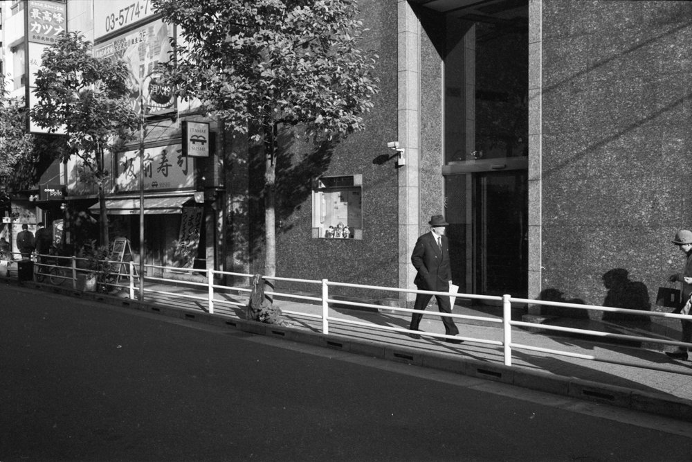 Lens-review-Leica-Summilux-pre-a-asph-infinity-lock-35mm-1.4-film-comparison-compare-Yurakucho-tokyo-japan-man-wearing-suit-walking-under-sunlight-f8-bw-kentmere-400-7elements-quality