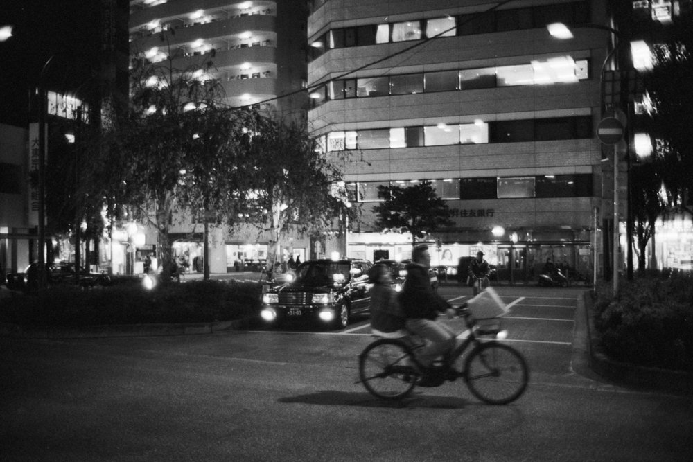 Lens-review-Leica-Summilux-pre-a-asph-infinity-lock-35mm-1.4-film-comparison-compare-around-Koenji-station-taxi-with-bike-passing-through-motion-blur-iflord-HP5-800-f1.4-wide-open-glow-halo