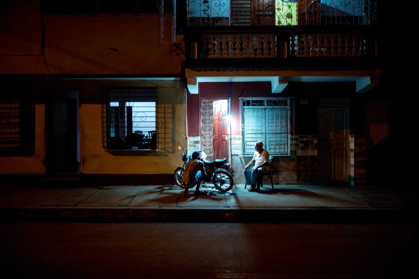 travel-cuba-cienfuegos-leica-m10-rangefinder-35mm-f2-summicron-iv-pre-a-trip-night-fixing-bike-outside-home