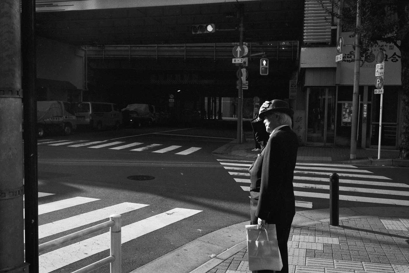 portfolio-we-have-seen-better-days-japan-tokyo-street-project-blog-photography-film-Yurakucho-day-Kentmere-400-leica-35mm-f1.4-35-summilux-infinity-lock-bw-black-and-white-old-man-with-hat-crossing-road
