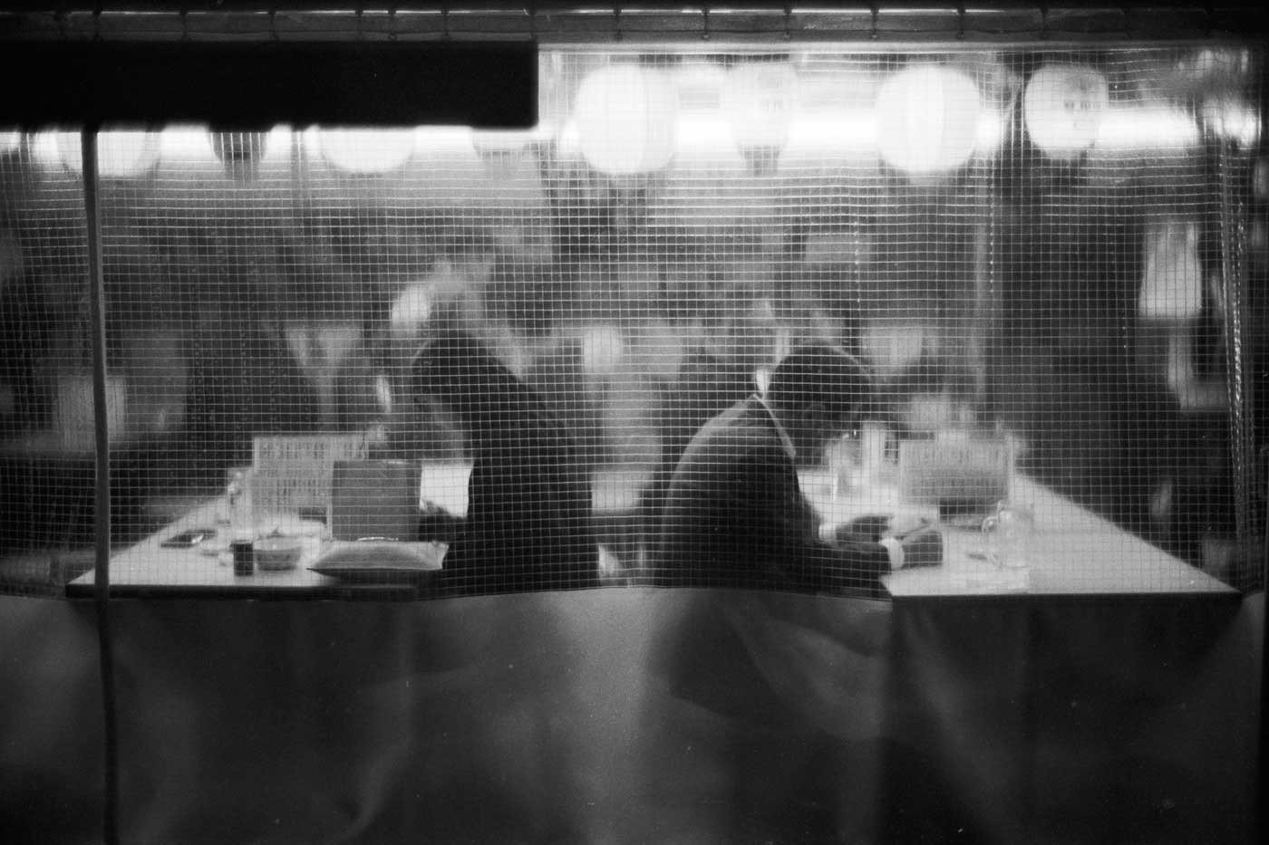 portfolio-we-have-seen-better-days-japan-tokyo-street-project-blog-photography-film-Yurakucho-day-Kentmere-400-leica-35mm-f1.4-35-summilux-infinity-lock-bw-sitting-behind-each-other-restaurant